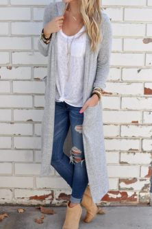 Woman wearing ripped and cuffed skinny jeans with a white T-shirt and long grey cardigan, together with beige ankle booties